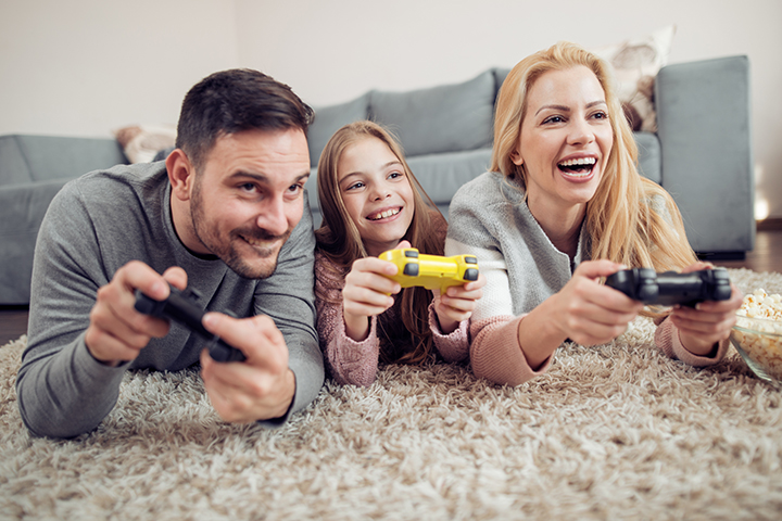mom, dad and daughter playing video games